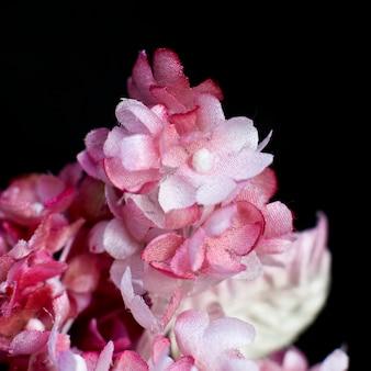 Rosa flieder auf schwarzem hintergrund. künstliche blumen