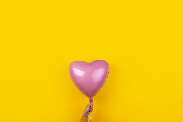 Rosa folienballon in form von herzen in der hand über gelbem hintergrund, glückliches 8. märz-tageskonzept