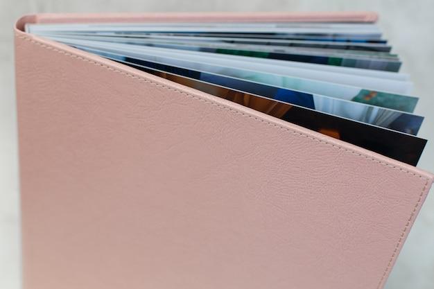 Rosa fotobuch mit einem hardcover auf einem holz. offenes familienfotobuch aus leder. erweiterte fotobuchseiten. hochzeitsfotoalbum öffnen. enthüllte seiten des familienfotoalbums. offenes album dreht sich