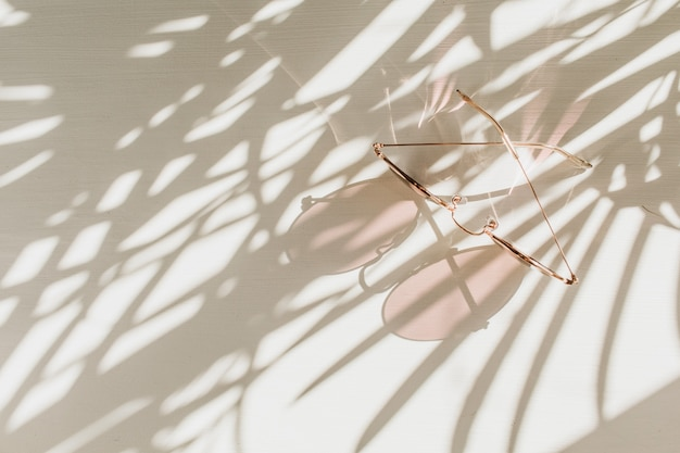 Rosa frauen-sonnenbrille auf weißem tisch mit blumenschatten