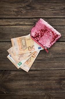Rosa frauenbrieftasche mit euro auf altem hölzernem hintergrund