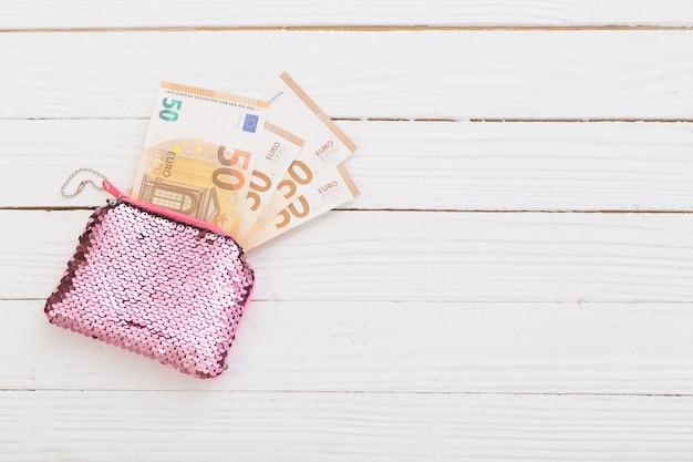 Rosa frauenbrieftasche mit euro auf weißem hölzernem hintergrund