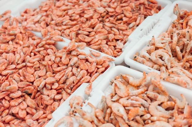 Rosa frische gefrorene garnelen mit eis in einem supermarkt oder in einem fischgeschäft. ungekochte meeresfrüchte hautnah. frisch gefrorene garnelen, delikatessen, meeresfrüchte-konzept,