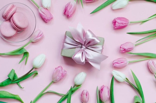 Rosa frische macarons mit geschenk und tulpen, draufsicht.
