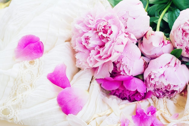 Rosa frische pfingstrosen und weißes hochzeitskleid, retro vintage-stil