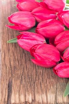 Rosa frische tulpenblumen auf grauem hölzernem hintergrund.