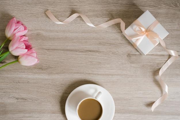 Rosa frühlingstulpen, eine geschenkbox und eine tasse kaffee. das konzept des frauentages oder des muttertags. flache lage mit kopienraum. frühlingsfest