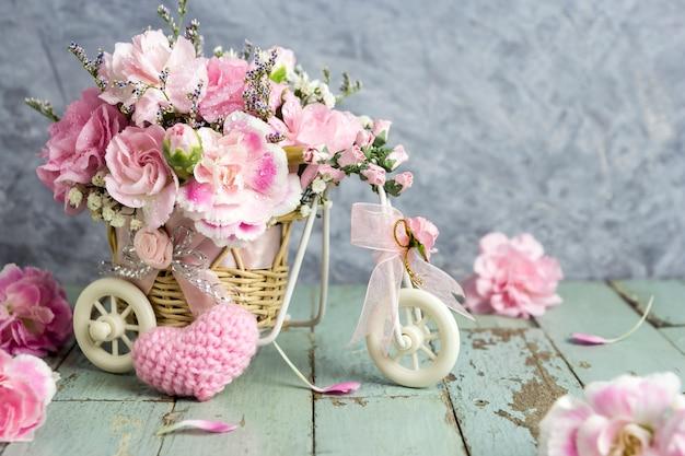 Rosa gartennelke im fahrrad mit rosa strickendem wollherzen auf altem holz