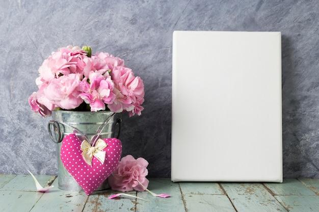 Rosa gartennelkenblume im zinkeimer und im leeren segeltuchrahmen auf weinleseholz