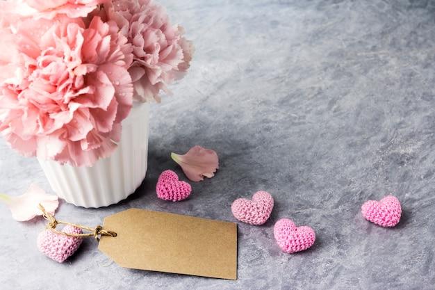 Rosa gartennelkenblume in der weißen schale mit leerem tag und herz des braunen papiers