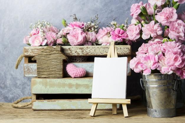 Rosa gartennelkenblumen und leerer segeltuchrahmen auf staffeleimalerei