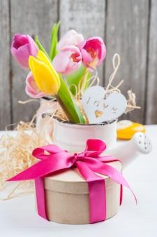 Rosa gelbe tulpen auf rustikalem hölzernem hintergrund