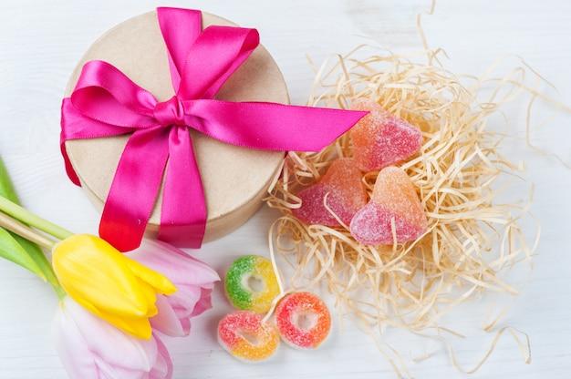 Rosa gelbe tulpen und geschenkbox mit rotem band