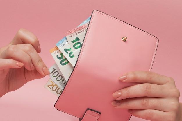 Rosa geldbeutel und eurobanknoten in den weiblichen händen auf rosa
