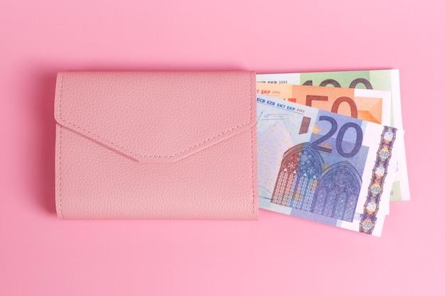 Rosa geldbörse auf pastellrosa hintergrund mit euroscheinen drin in
