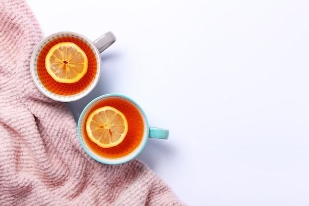Rosa gemütliches plaid und zwei tassen tee mit zitrone auf weißem hintergrund. draufsicht, flache lage. speicherplatz kopieren. tee für herbst oder winter.