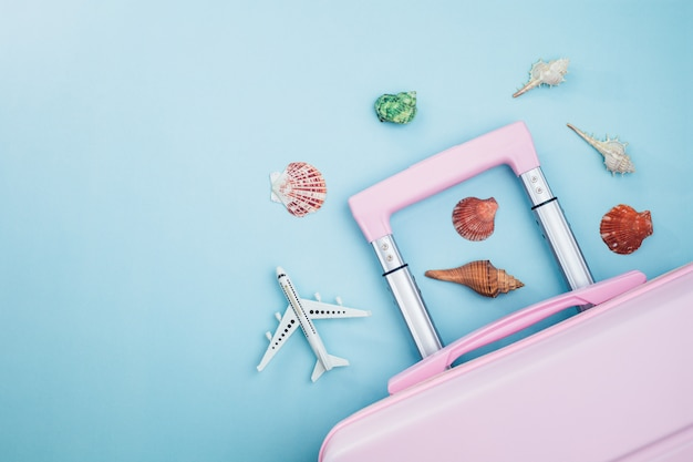 Rosa gepäck mit weißem flugzeugmodell und muscheln auf blau für reisen und sommerstrandkonzept