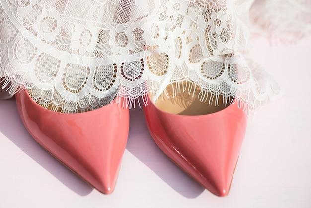 Rosa gerichtsschuhe und spitzenkleid auf rosa hintergrund