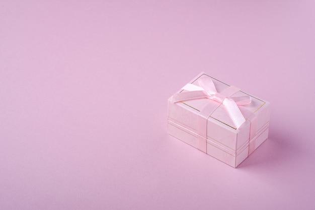 Rosa geschenkbox mit band auf weichem rosa hintergrund, winkelansicht, kopienraum