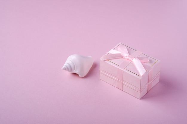 Rosa geschenkbox mit band nahe der weißen muschel auf weichem rosa hintergrund, winkelansicht, kopienraum