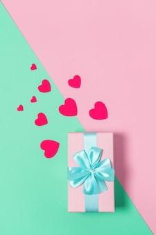Rosa geschenkbox mit blauer schleife auf pastell zweifarbigem hintergrundrosa und minze, kopierraum, flache lage. 8. märz, 14. februar, geburtstag, st. valentinstag, mutter, frauentag feier konzept. vertikal
