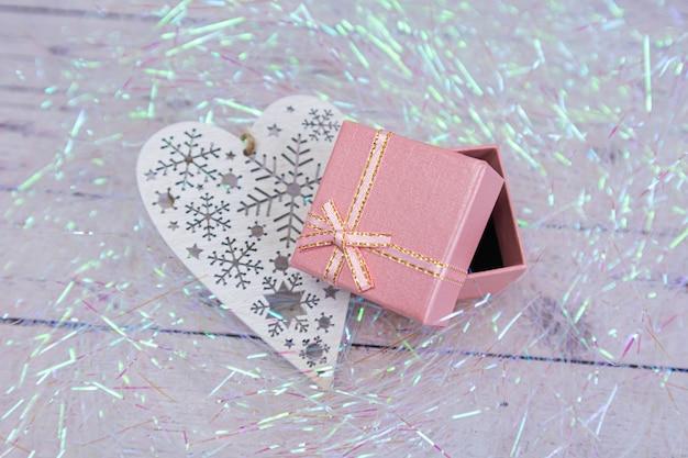 Rosa geschenkbox mit goldener schleife. geschenkverpackung für einen urlaub. in der nähe liegt ein weißes durchbrochenes herz aus holz.
