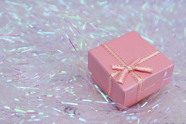 Rosa geschenkbox mit goldener schleife liegt. geschenkverpackung für einen urlaub.