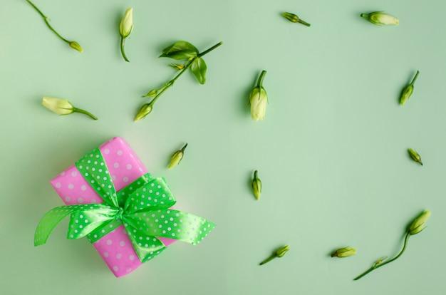 Rosa geschenkbox oder geschenk mit band auf pastellgrün