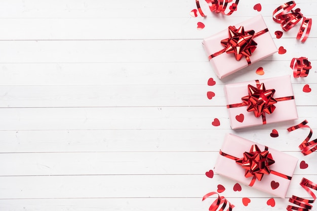 Rosa geschenkboxen mit roten bändern und bögen, konfettiherzen auf einem weißen hintergrund. textfreiraum flach legen. grußkarte für geburtstagsfeier, hochzeit valentinstag.