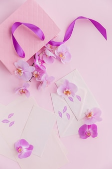 Rosa geschenktüte und fliegende orchideenblumen auf hellrosa hintergrund