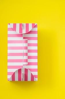 Rosa gestreifte geschenkbox auf gelbem hintergrund