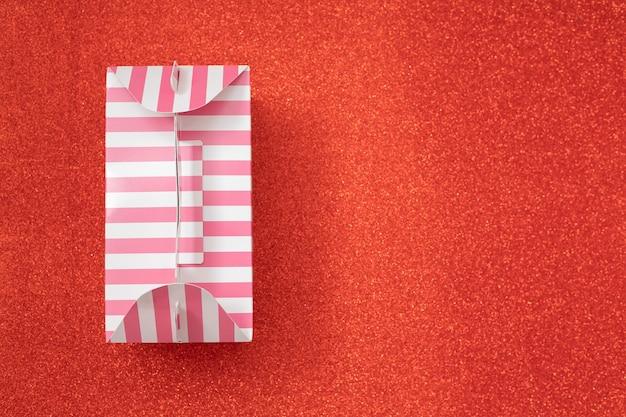Rosa gestreifte geschenkbox auf orange hintergrund