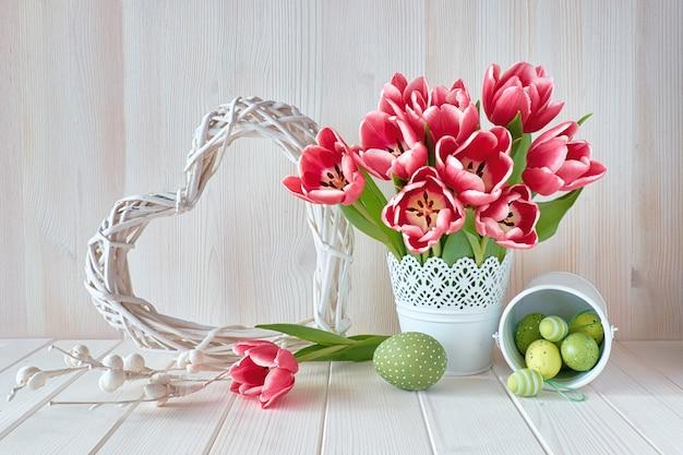 Rosa gestreifte tulpen, ostereier und geflochtenes herz