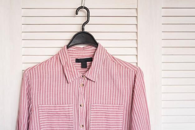 Rosa gestreiftes hemd, das an einem kleiderbügel hängt. weißer holzschirm auf der oberfläche. modische garderobe