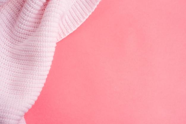 Rosa gestrickte kleidung auf einem rosa papierhintergrund