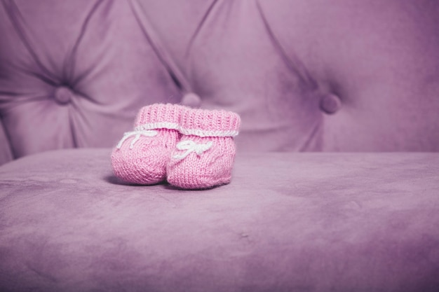 Rosa gestrickte kleine babyschuhe, nahaufnahme, die auf der couch steht