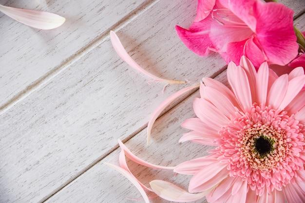 Rosa gladioleblumen-frühlingssommer und -blumenblatt des gerberas verzieren auf weißem hölzernem
