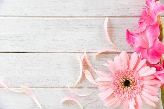 Rosa gladiolenblumenfrühlingssommer und -blumenblatt des gerbera verzieren auf weißem hölzernem hintergrund