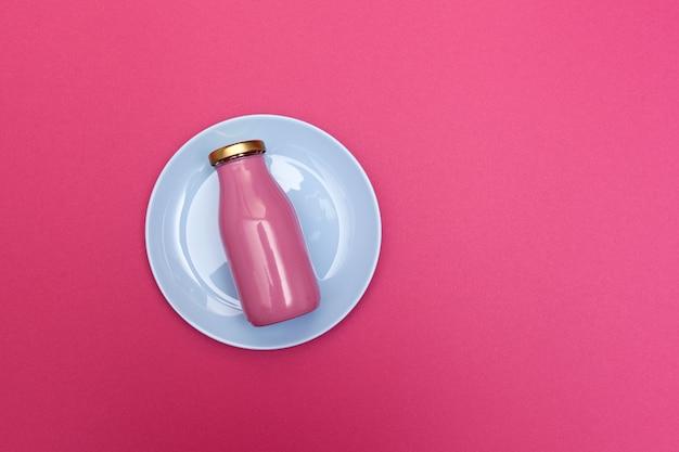 Rosa glasflasche mit goldenem deckel auf teller. draufsicht, kopierraum. gesundes fruchtgetränk mit kollagen.