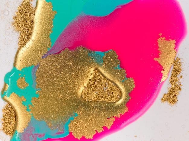 Rosa, goldene und blaue gemischte tinten verschütteten auf weißem papierhintergrund. goldene glitzer-textur.