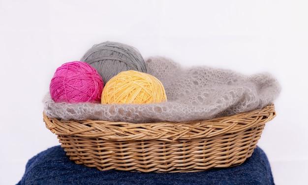 Rosa graue und gelbe fadenbälle zum stricken in einem korb und grauer schal auf hellem hintergrund stricken...