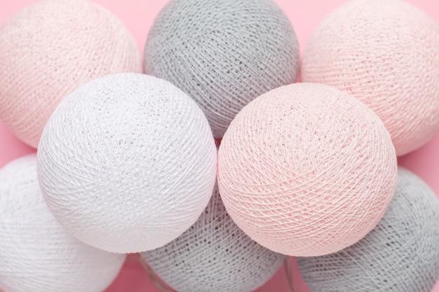 Rosa, graue und weiße kugeln girlande auf einem pastell