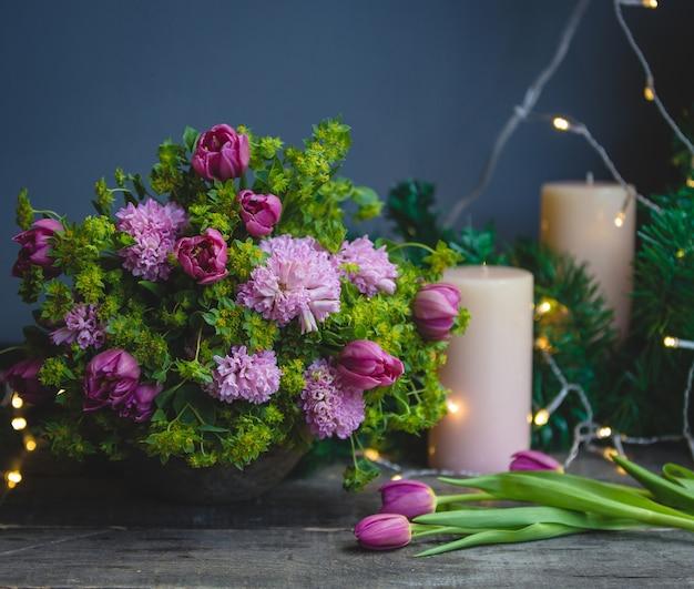 Rosa grüner blumenstrauß, tulpen und kerzen mit weihnachtslichtern herum
