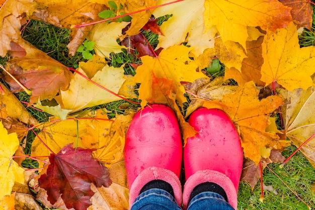 Rosa gummistiefel auf nassen gelben blättern. begriffsbild von beinen in den stiefeln auf dem herbstlaub.