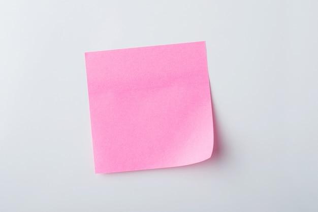 Rosa haftnotiz auf weißer wand
