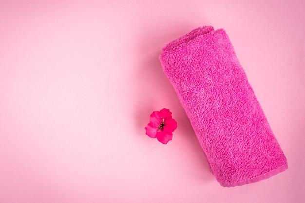 Rosa handtuch mit blume auf rosa hintergrund