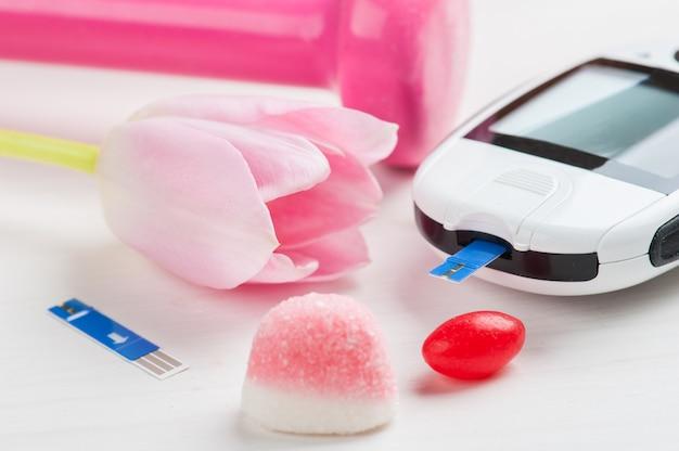 Rosa hantel, süßigkeiten und blutzuckermessgerät