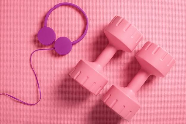 Rosa hanteln und kopfhörer auf der fitnessmatte