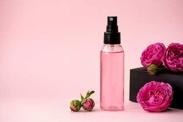 Rosa hauttonikum in einer plastikflasche mit rosenblüten