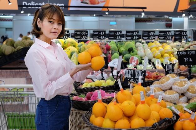 Rosa hemd der asiatischen frauenabnutzung beschließen, obsteinzelteile in den supermärkten zu kaufen